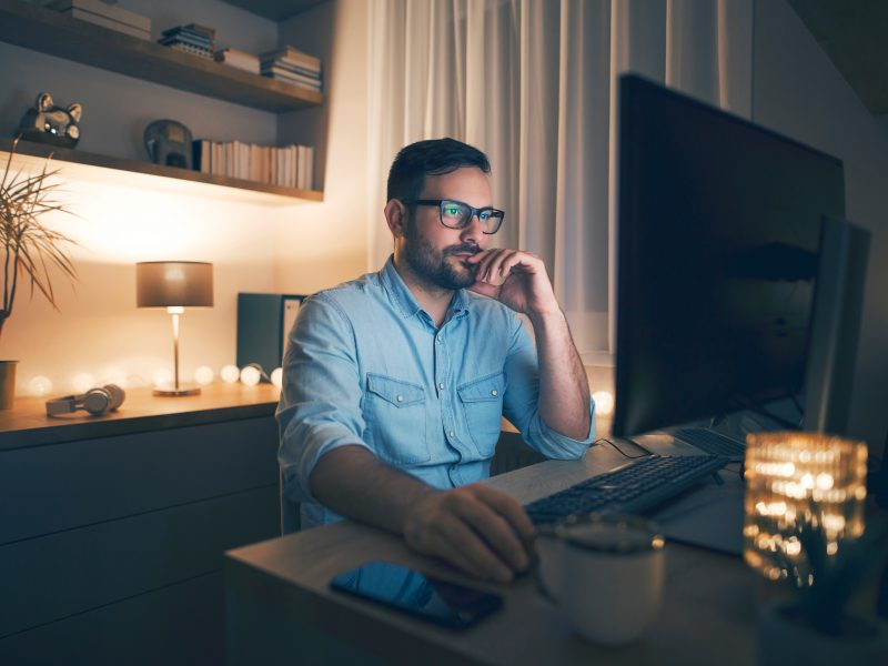 Young,Pensive,Man,Working,Remotely,From,Home,At,Night.